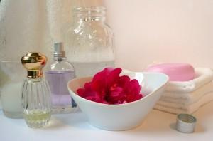 Porcelanowe pojemniczki i szklane flakoniki jako dekoracja romantycznej łazienki