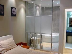 Szklane drzwi przesuwne między małżeńską łazienką a sypialnią