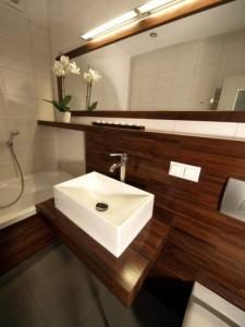 Poziome lustro w drewnianej oprawie nad umywalką